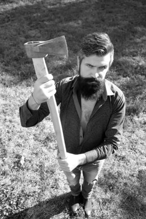 logger: Top full length view of one handsome strong stylish male logger of young man with long lush beard and moustache in shirt holding wooden axe standing on grass outdoor black and white, vertical picture