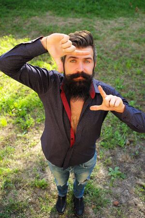 sexy funny: Top full length view of one handsome strong stylish male logger of young man with long lush black beard and moustache in shirt standing on green grass outdoor holding hands in gesture, vertical photo Stock Photo
