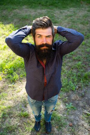 black head and moustache: Top full length view of one handsome strong stylish male logger of young man with long lush black beard and moustache in shirt standing on green grass outdoor holding hands on head, vertical picture