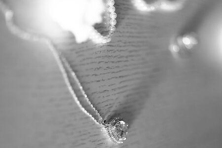 diamante negro: Primer ornamento elegante colgante de joyería en forma de corazón con cristales y perlas de cuerda sobre fondo blanco y negro borrosa, cuadro horizontal