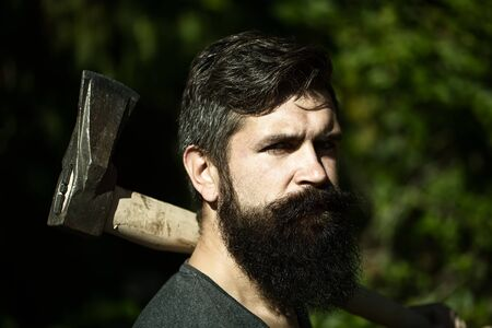 logger: One handsome strong stylish male logger of young man with long lush black beard and moustache in shirt holding wooden axe standing in forest outdoor on natural background, horizontal picture