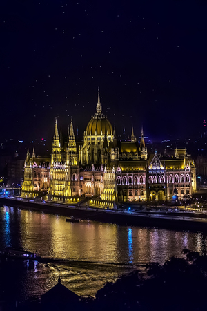 lak�hely: Awesome hungarian residency parliament with cupolas and spires standing on river danube largest historical building illuminated by colorful lights at night budapest hungary copyspace, vertical