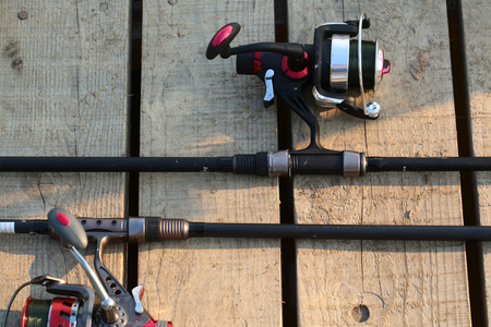 inertial: Closeup silhouette of pair of fish-tackle fishing spinning rods and reels with black colored angling line over natural wooden cover background, horizontal picture