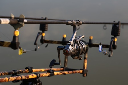inertial: Closeup silhouette of fish-tackle fishing rods reel and rings with gray blurred natural water background, horizontal picture Stock Photo