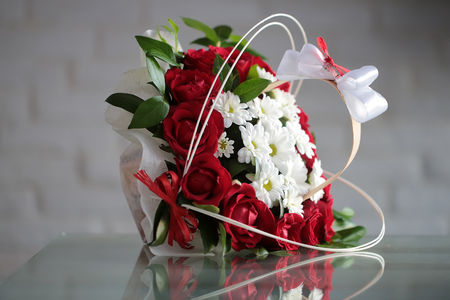 sidelong: Beautiful bunch of fresh red roses white chrysanthemums decorated with green leaves bows lies sidelong on glass table on blurred gray background, horizontal picture