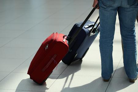 maleta: vista posterior Detalle de las piernas femeninas en pantalones vaqueros con maleta con ruedas de color rojo que se colocan en la cola detrás de azul bolsa de viaje con ruedas sobre el aeropuerto de fondo terminal de suelo de baldosas, cuadro horizontal