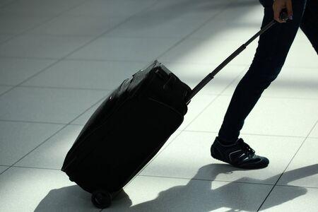 piernas: Vista posterior Primer plano de piernas femeninas en pantalones vaqueros con el caso maleta con ruedas negro bolsa de viaje con ruedas carro en movimiento sobre el aeropuerto de fondo del terminal baldosa, cuadro horizontal