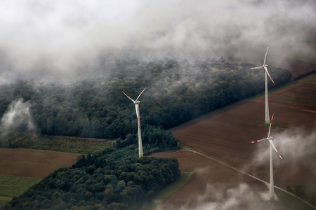 energy picture: Panorama spectacular skyline view of cloudy blue sky from airplane window over windfarm landscape background wind turbines renewable power energy stations, horizontal picture