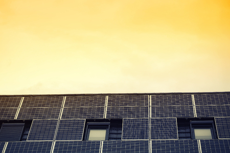 monocrystalline: Closeup photovoltaic solar panels on house roof with open windows and  with shut blinds against sunny yellow sky renewable power energy, horizontal picture Stock Photo