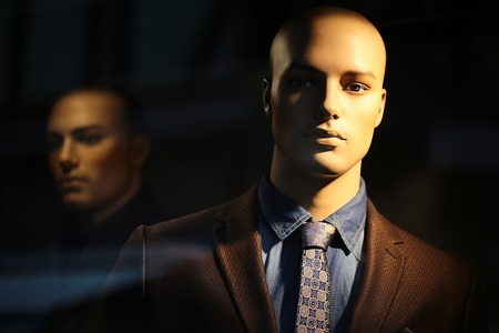 Closeup portrait of illuminated bald-headed fashion mannequin wearing casual male suit made of thready cloth jacket tie shirt denum in shop window over blur one background, horizontal picture