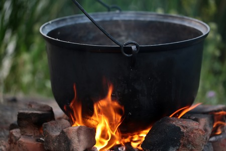 caldron: Closeup cooking in cauldron licked by flames on open fire fireplace made of bricks stones in field conditions over blurred nature background, horizontal picture