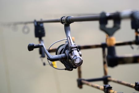inertial: Closeup silhouette of fish-tackle fishing reel rods and rings with gray blurred natural water background, horizontal picture