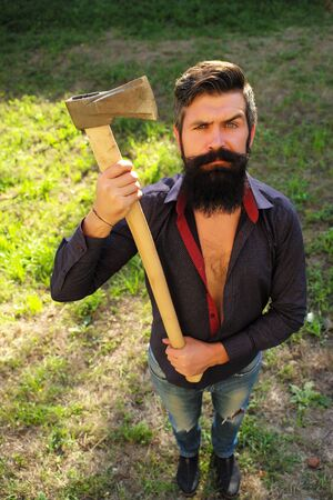 logger: Top full length view of one handsome strong stylish male logger of young man with long lush black beard and moustache in shirt holding wooden axe standing on green grass outdoor, vertical picture