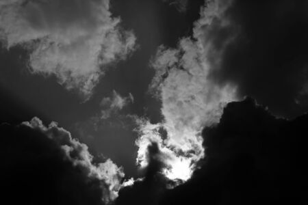 screened: Panorama spectacular seamless cloudy skyline view sun screened by bank of dark clouds threaten rain from bottom upwards breath-taking celestial background black and white, horizontal picture Stock Photo