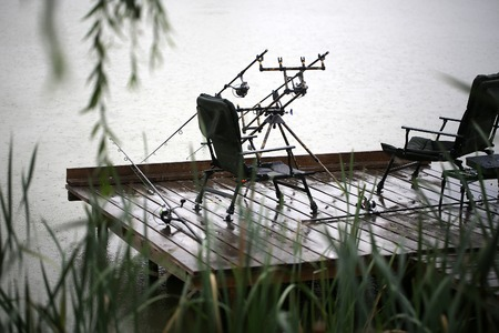 inertial: Fishing tackle gear two convertible chairs stay outdoor in rain drops falling plop into water on wet wooden pier over natural rainy day background, horizontal picture Stock Photo