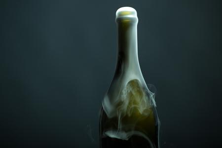 Close-up uitzicht op een nieuwe open volledige champagme wive zoet of droog drank groene glazen fles met mooie witte rook voor kerstmis of nieuwe jaar in de studio op een grijze achtergrond, horizontaal beeld