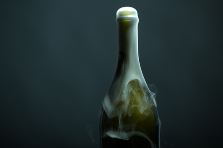Closeup view of one new open full champagme wive sweet or dry drink green glass bottle with beautiful white smoke for celebration christmas or new year in studio on grey background, horizontal picture