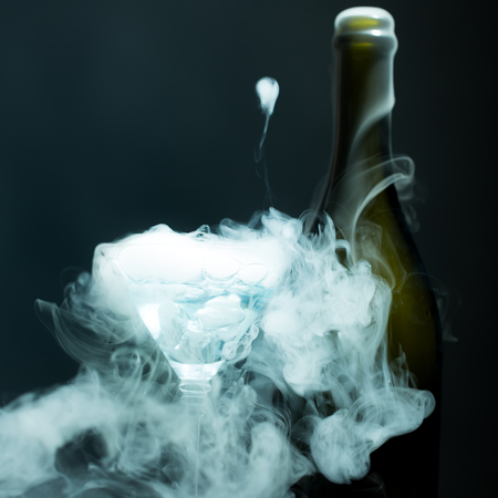 Closeup of new open full champagme wive sweet or dry drink green glass bottle and goblet with beautiful white smoke for celebration christmas or new year in studio on grey background, square picture