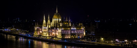historic place: Wonderful panorama view of illuminated hungarian legislative building parliament in gothic revival style famous historic place across river danube at night budapest hungary europa, horizontal picture
