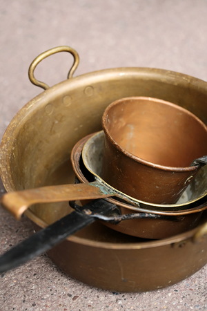 basins: Closeup corroded old vintage used copper cooking pots ladles basins with handles stacked on stone floor background, vertical picture