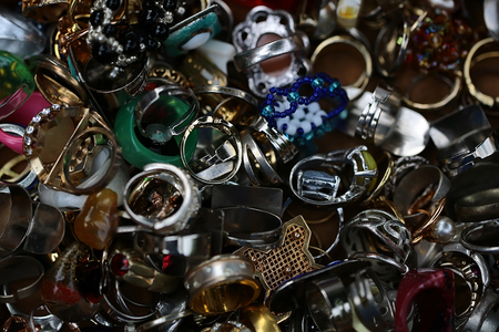 dozens: Variety dozens different colour golden silver old-fashioned time-worn used vintage bijouterie collection of imitation jewellery frosted transparent glazy dum finger-rings piled together, horizontal picture