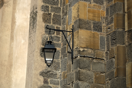 Fragment of facade of typical time-worn gray stone house with old style street-lamp closeup on seamless background, gorizontal picture