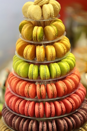 display stand: Closeup assortment of lots of multicolored tasty french macarons on tier circle cake tower display stand pyramid-shaped made of clear plastic on many visible levels over blur background, vertical picture