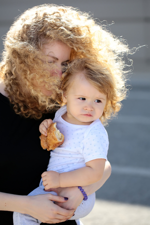 wind blown hair: Closeup portrait of attractive young mother holding her cute baby in arms blown hair with wind serene family scene on solar background, vertical picture