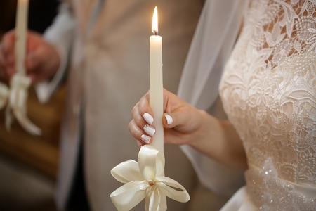 Beautiful Bride In Laced Dress And Groom Holding Burned Candles Decorated By White Ribbon Bow At
