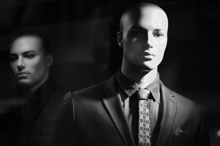 Closeup portrait of illuminated bald-headed fashion mannequin wearing casual male suit made of thready cloth jacket nasal in tone tie shirt over blur one black and white, horizontal picture