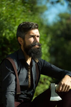 logger: One handsome strong stylish male logger of young man with long lush black beard and moustache in shirt holding wooden axe sitting in forest outdoor on natural background, vertical picture Stock Photo