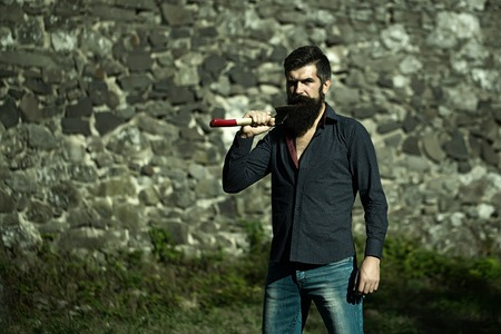 logger: One handsome strong stylish male logger of young man with long lush black beard and moustache in shirt holding wooden axe standing near grey stone wall outdoor, horizontal picture Stock Photo