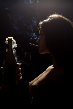 Closeup portrait side view of one young sexy woman with naked chest holding uncorked glass champagne wine bottle with smoke and smoking cigarette in studio on black background, vertical picture