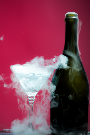 Closeup of glamour open full champagme wive sweet or dry drink green glass bottle and goblet with beautiful white smoke for celebration christmas or new year on pink background, vertical picture Standard-Bild