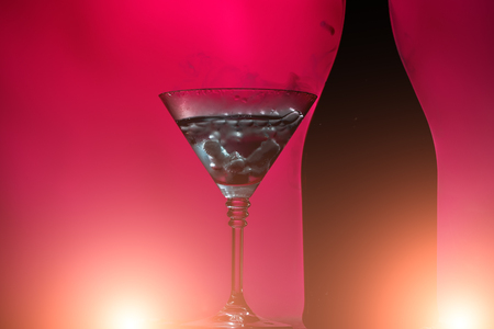 Closeup of glamour open full champagme wive sweet or dry drink green glass bottle and goblet with white smoke and ice for celebration christmas or new year on pink background, horizontal picture