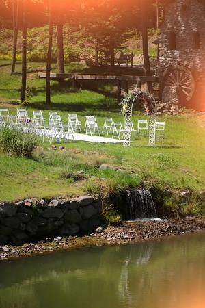 molino de agua: Centrarse en decorado con flores de la boda del arco sillas blancas sendero para llevar a cabo la ceremonia en la orilla del lago con molino de agua faterfall puntos de luz sobre fondo de paisaje arbolado, imagen vertical