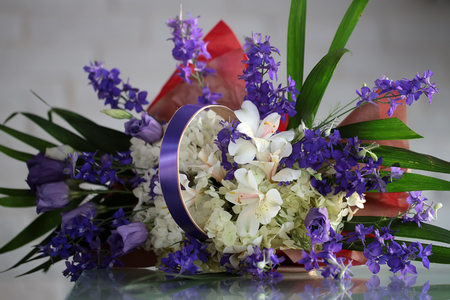 sidelong: Closeup beautiful bunch of fresh tender white and violet flowers mixed decorated with green leaves in paper packet with handle  lies sidelong on glass table on blurred gray background, horizontal picture