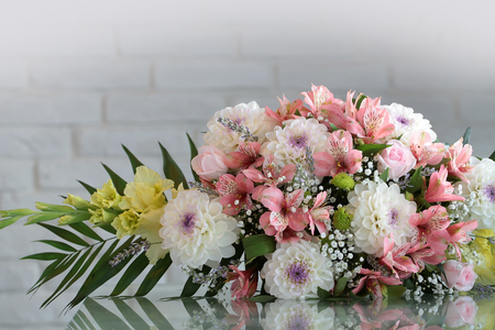 sidelong: Closeup beautiful bunch of fresh tender flowers in white and rosy colores yellow gladioluses mixed decorated with green leaves lies sidelong on glass table on blurred gray background, horizontal picture Stock Photo