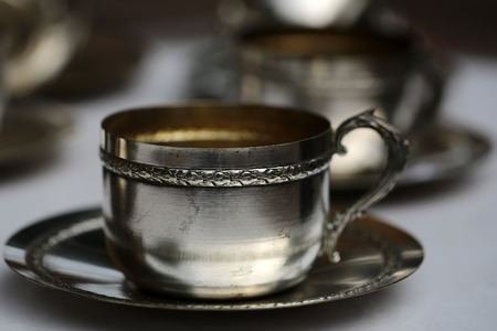 used ornament: Closeup beautiful old vintage used shiny german silver tea cup with saucer with floral ornament on blur tea-set background, horizontal picture Stock Photo
