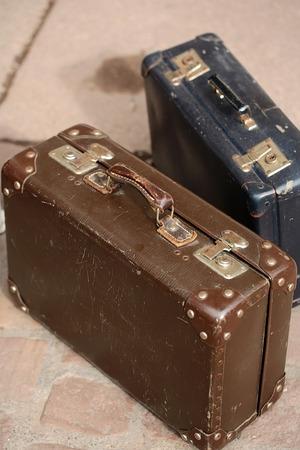 돌 타일 바닥 배경 위에 서있는 가죽 핸들 금속 buttonheads 및 키 잠금과 두 아름 다운 구식 빈티지 갈색 파란색 가방의 근접 촬영 컬렉션, 세로 그림