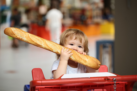 crackling: Closeup portrait of beautiful pretty cute hazel-eyed kid with shoulder-length blond wavy hair holding and biting French bread riding red and blue shopping trolley against grey background, horizontal