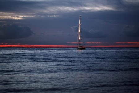 red sunset: Beautiful calm evening seascape with yacht sailing in dark blue seaways under bare poles floating in the sea in rays of amazing red sunset on horizon against red and blue cloudy sky, horizontal photo Stock Photo