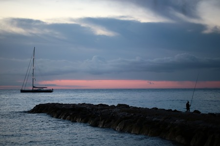 horison: Beautiful calm evening seascape with rocks and one fisherman in foreground and dark silhouette of yacht floating in the sea after amazing red sunset and low dark blue clouds on horison,  horizontal picture