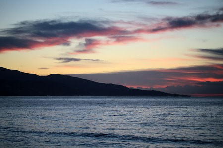 under view: Magic evening seascape view on closeup calm blue waterways of see with dark mountain silhouette in dusk on horizon under bright dark and light red rosy and blue sky with low cloud cover, horizontal picture