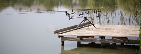 fluvial: Two carp carbon fishing rods spinning reels with spoon on support standing at wooden pier in lake and green reed spring male activity outdoors on natural background, horizontal picture Stock Photo