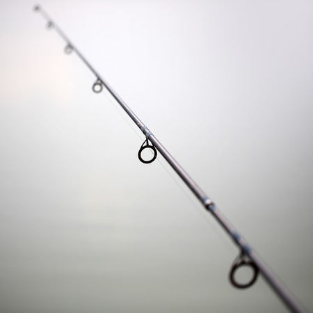 grey water: Closeup of black carbon fishing rod with line against of grey water background male activity outdoor vacation, square picture