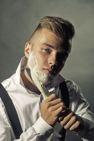 stays: One young handsome sensual man shaving his face with knife and foam looking at camera with unbutton collar keeping his shirt stays in studio on black background black and white, vertical picture
