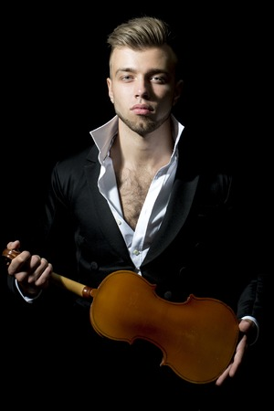 unshaven: One young handsome sensual unshaven bearded man looking at camera with popped unbutton collar white shirt black jacket keeping violin stays forward in studio on black background, vertical picture