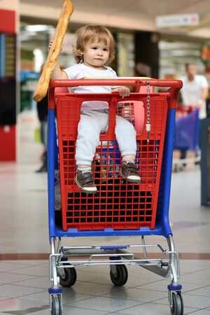 shopping trolley: Closeup beautiful cute baby holding and biting French bread sitting in red and blue shopping trolley against supermarket full of people background, vertical picture