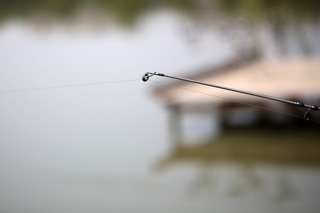 sportfishing: Closeup of carbon fishing tackle with lure on natural blur background outdoor male hobby angling vacations relax, horizontal picture